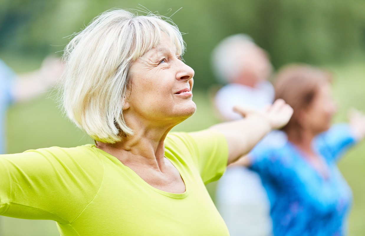 Older lady stretching arms out in outside exercise class